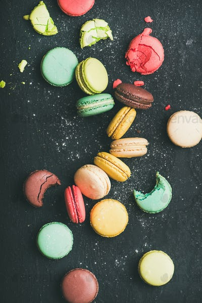 Flat-lay of sweet colorful French macaroons over black background