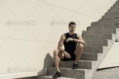 Strong sportsman sitting at the base of ascending stairs with su