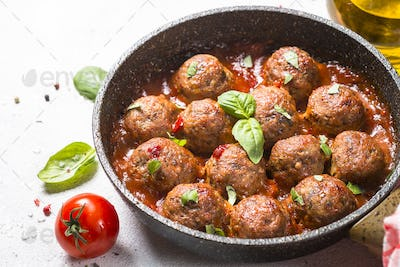 Meatballs in tomato sauce on white table