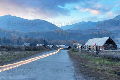 xinjiang hemu village in sunset and light streaks on road from motorbike