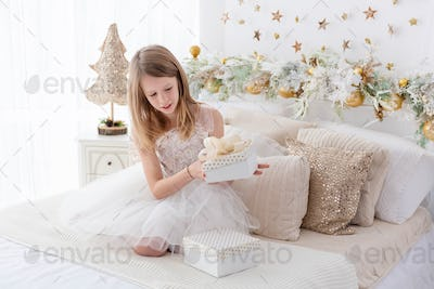 Girl sitting on bed, opening Christmas gifts