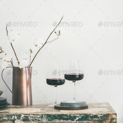 Two glasses of red wine over rustic countertop, square crop