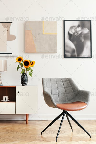Grey armchair and sunflowers on cabinet in white living room int
