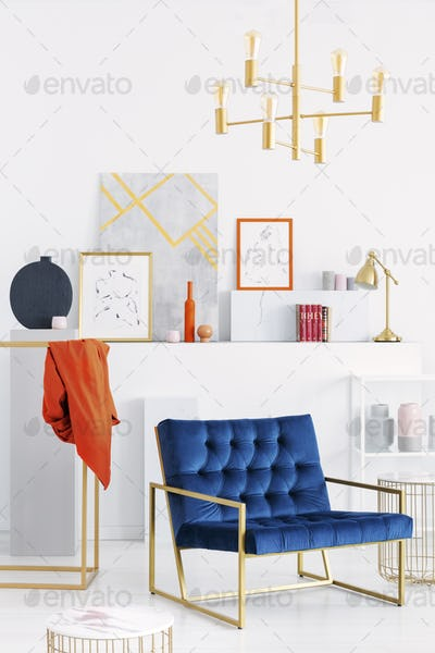 Vertical view of golden chandelier above petrol blue settee in w
