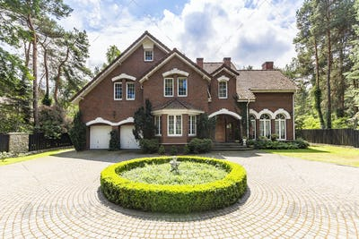 Front view of a driveway with a round garden and big, english st