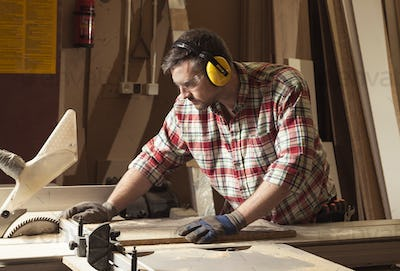 Worker in protective glasses and headphones cutting wood in a sa