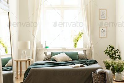 Bedroom interior in nature colors with big bed, gray and green l