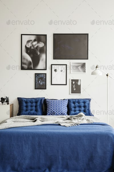 Patterned pillows on bed in navy blue and white bedroom interior