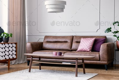 Pillows on leather couch in retro living room interior with lamp