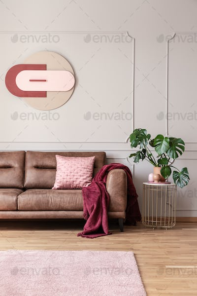 Poster above leather sofa in bright living room interior with ca
