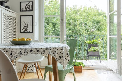 Real photo of a scandi dining room interior with a patterned clo