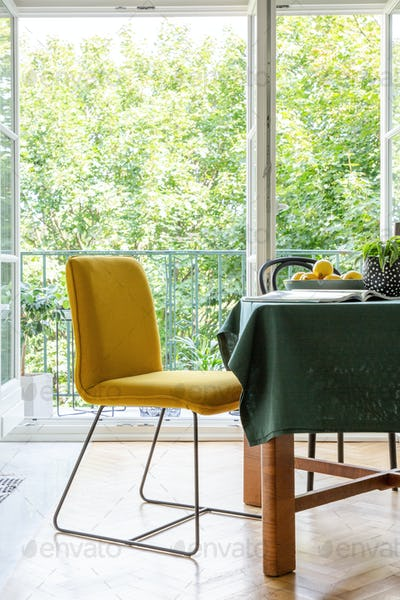 Yellow chair next to a table in a dining room interior with a te