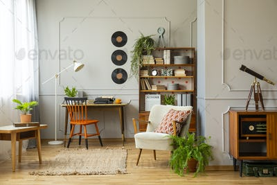 Rug between armchair and wooden table in retro apartment interio