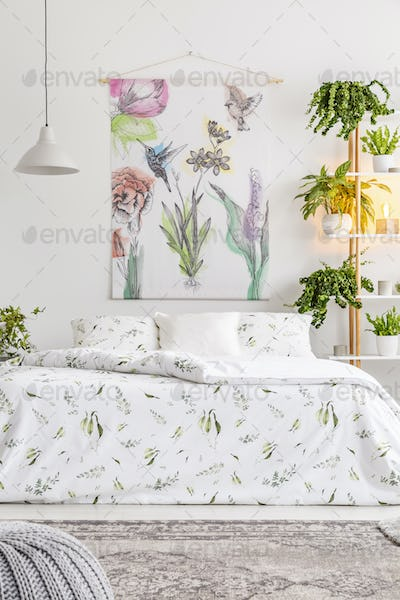 Natural bright bedroom interior with a comfortable bed dressed i