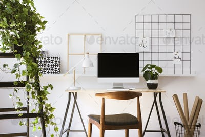 Real photo of wooden desk with metal lamp, fresh plant and empty