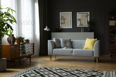 Dark living room interior in real photo with window with curtain
