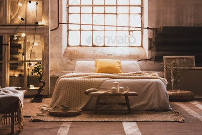 Lights on shelves next to bed with sheets and pillows in bright