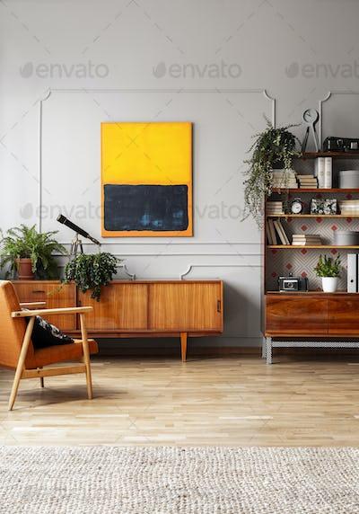 Orange painting above wooden cupboard in retro flat interior wit