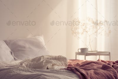 Red blanket on bed with pillows in white minimal bedroom interio