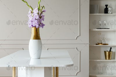 Lavender purple flowers in a golden vase on a white marble table