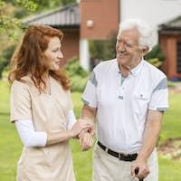 Smiling grey-haired senior man with a walking stick talking talk