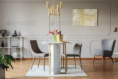 Real photo of an elegant dining room interior with golden accent
