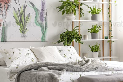 Urban jungle bedroom interior with plants in pots beside a bed d
