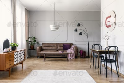 Real photo of light grey living room interior with window with c