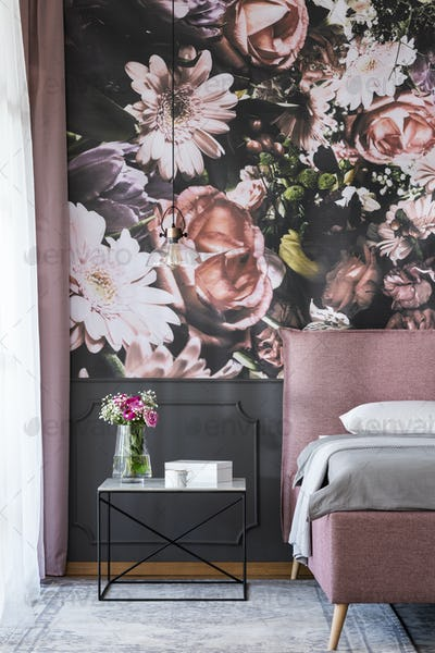 Flowers on table next to pink bed in bedroom interior with patte