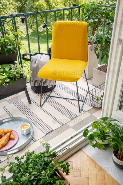 High angle view of a vibrant yellow chair and home plants on a p