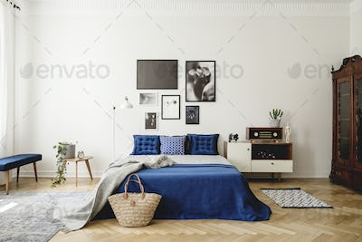 Navy blue bed with blanket next to cabinet with radio in retro b