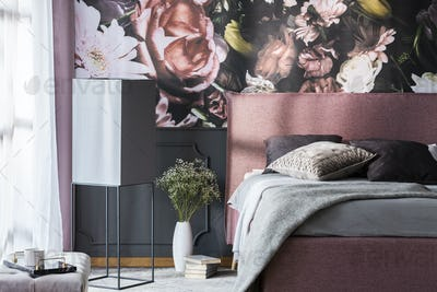 Flowers and books next to pink bed with grey pillows in patterne