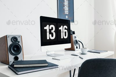 Close-up of a white desk with spiral notepads, speakers and a mo