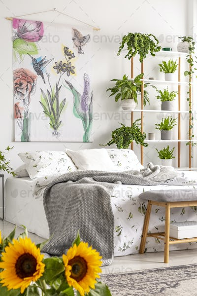 Urban jungle bedroom interior with sunflowers in the foreground