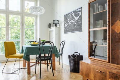 Retro dining room interior with a table, chairs and cupboard in