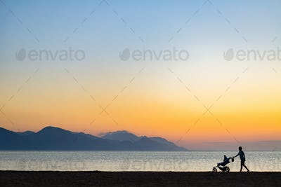 Silhouette of mother with baby stroller enjoying motherhood at s