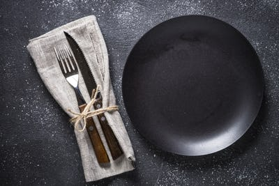Black plate, cutlery and napkin on stone table top view