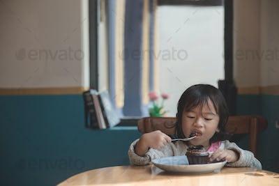 Asian little girl eating cake