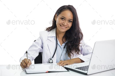 beautiful young doctor working on her laptop and writing on note