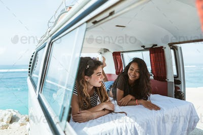two young woman lay down relax inside of retro van