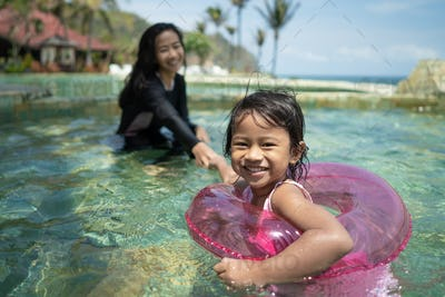 Attractive little girl and her mother swimming