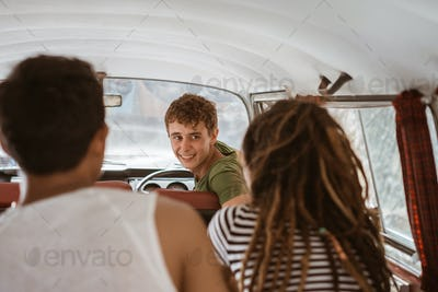 happy young people having fun inside retro van on trip