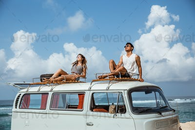 young couple with sunglasses sitting on top of minivan roof