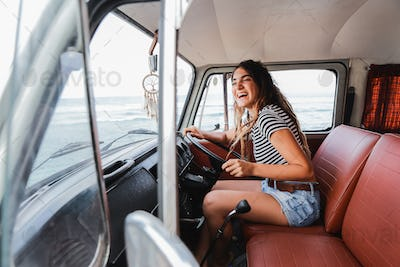 young woman driver smiling on road trip