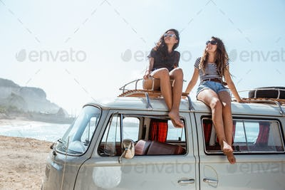 young women with sunglasses sitting on top of minivan roof
