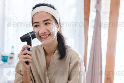 asian woman using electric face washer
