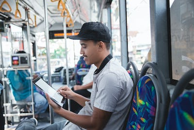 Man traveling by bus and using a tablet