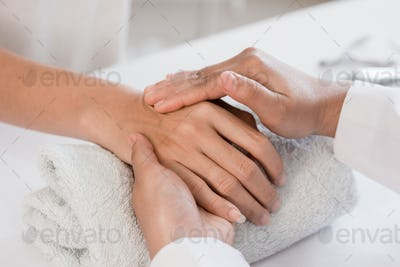 Young woman is getting a hand massage with beautician