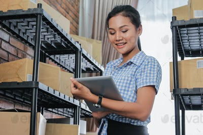 asian entrepreneur woman with package shelf