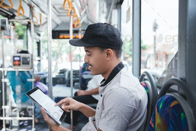 asian man traveling by bus and using a tablet
